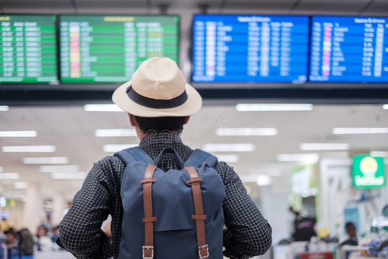 Handelsresande f?r ung man med tid f?r kontrollerande flyg f?r hatt, asiatisk passagerare som ser till informationsbr?det i termi royaltyfria bilder