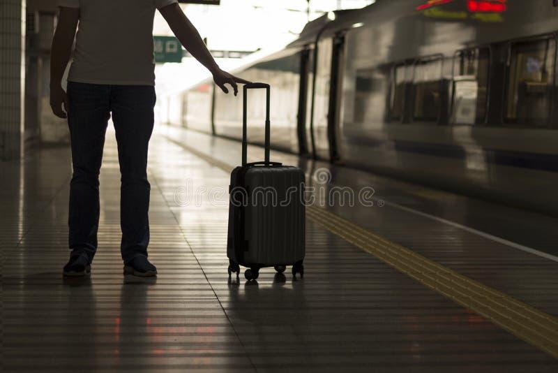Handelsresande med en resväska på plattformen på järnvägsstationen royaltyfria bilder