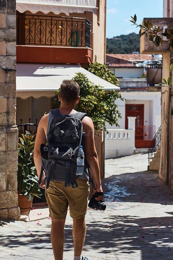 Handelsresande med kameran och ryggsäck som går till och med den utländska staden, Creta, Grekland arkivfoto