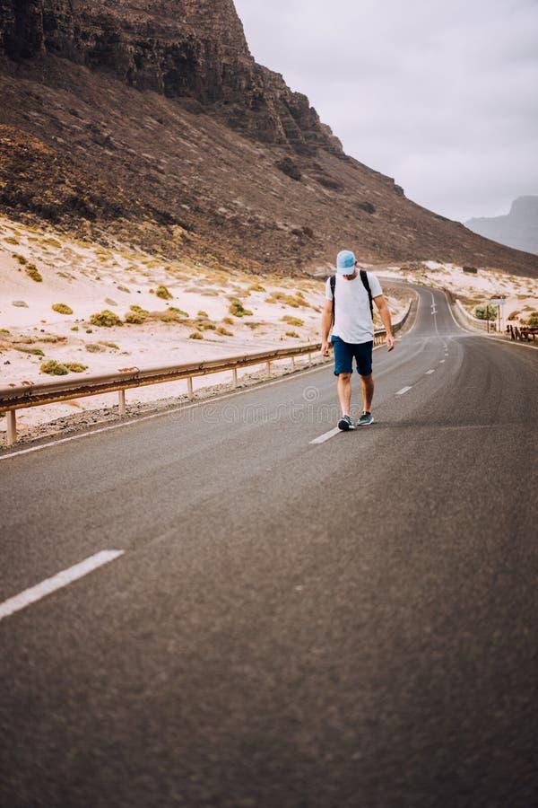 Handelsresande med ryggsäckanseende i mitten av en episk slingrig väg Enorma vulkaniska berg i avståndet bakom arkivfoto