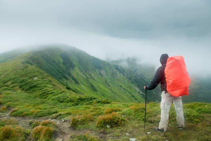 Handelsresande med ryggsäcken i bergen i molnen royaltyfri foto
