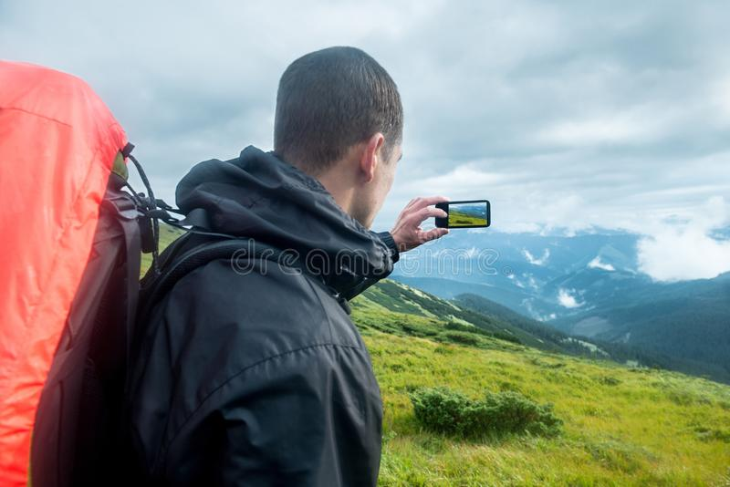 Handelsresande med ryggsäcken och smartphonen på bergen royaltyfri bild