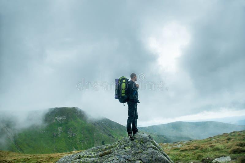 Handelsresande med ryggsäcken på överkanten av berget i molnen arkivfoto