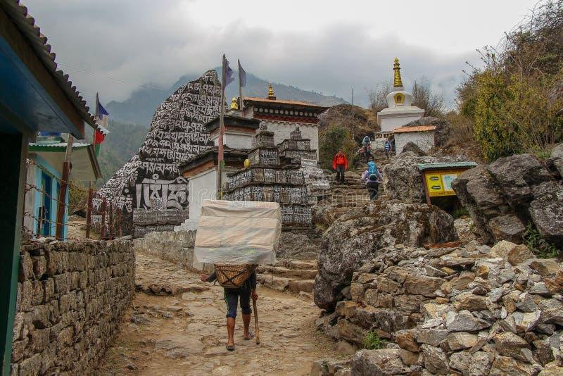 Handelsresande och portvakter går förbi de mani stenarna och den buddistiska stupaen i Nepal arkivfoto