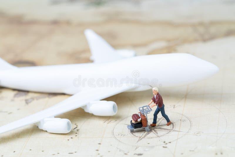 Handelsresande- och trans.begrepp, miniatyrvuxen man med flygplatsvagnen och bagage med leksakflygplanet på tappningvärldskarta royaltyfri foto