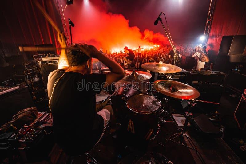 Handelsresande på etapp kontur av musikmusikbandet i handling på musiketapp rockbandet för populär musik utför på etapp royaltyfri bild