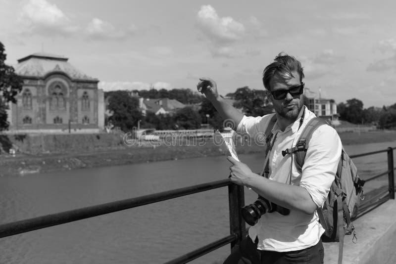 Handelsresande på flodbanken som försöker att finna vägen royaltyfri bild