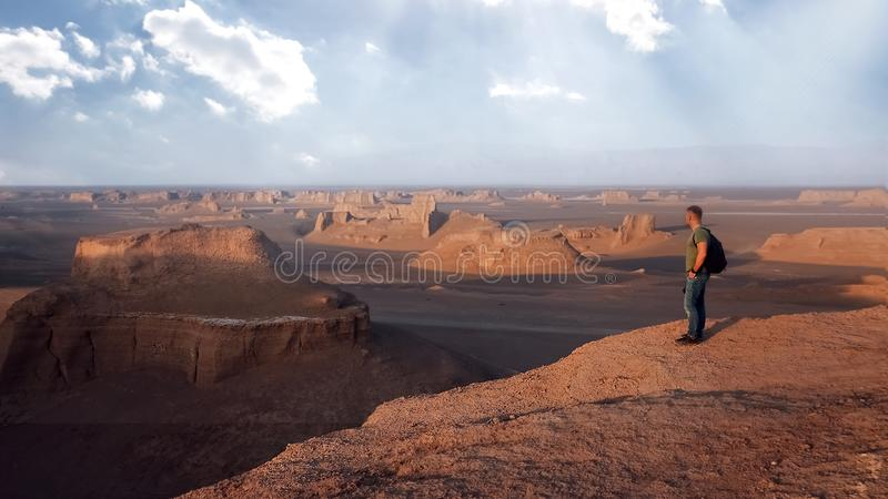 Handelsresande p? bakgrunden av steniga bildande i den Dasht e Lut ?knen iran natur persia royaltyfri bild