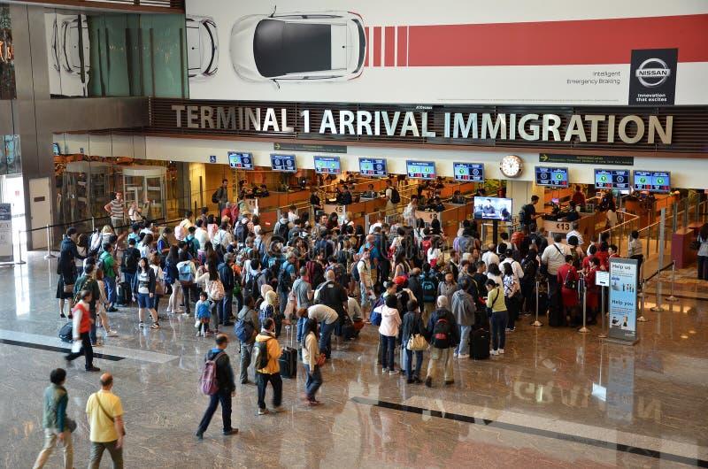 Handelsresande skriver in invandringkontroll på den Changi internationalen Airp arkivfoton