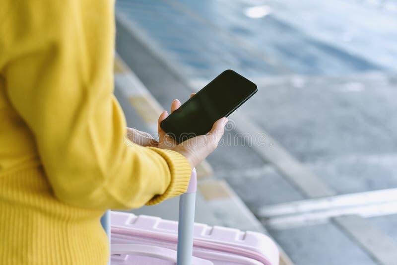 Handelsresande som använder smartphoneapplikationen för att boka taxibilservice på flygplatsen fotografering för bildbyråer