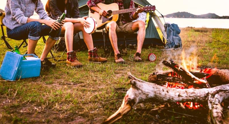 Handelsresande som campar g?ra picknicken och spela musik i ?ngf?lt Berg- och sj?bakgrund Folk och livsstilbegrepp royaltyfria foton