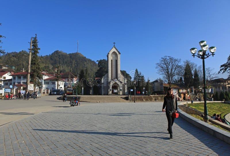 Handelsresande som framme går på trottoaren av fyrkanten av den katolska heliga radbandkyrkan i Sapa royaltyfri fotografi