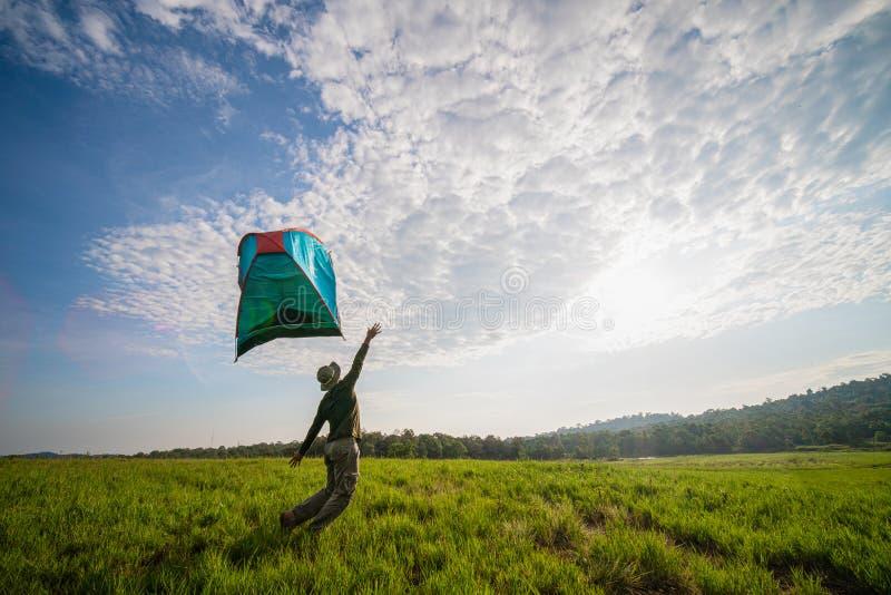 Handelsresande som har att campa med ett tält på gräsfält och vindslagtältet bort royaltyfria bilder