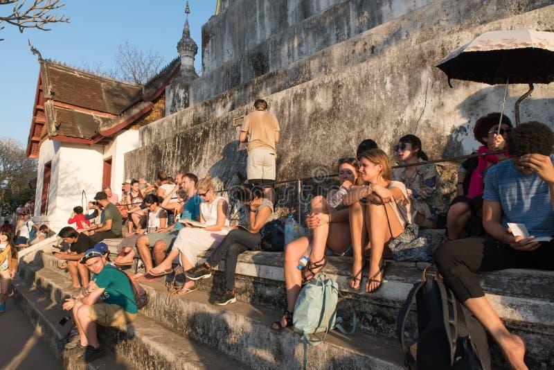 Handelsresande som väntar på hållande ögonen på solnedgång på den Phu sitemplet, Luang Pr royaltyfria bilder