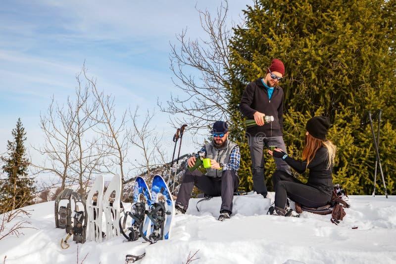 Handelsresande vilar i vintern i bergen Företaget av ungdomarpå ett stopp arkivfoto