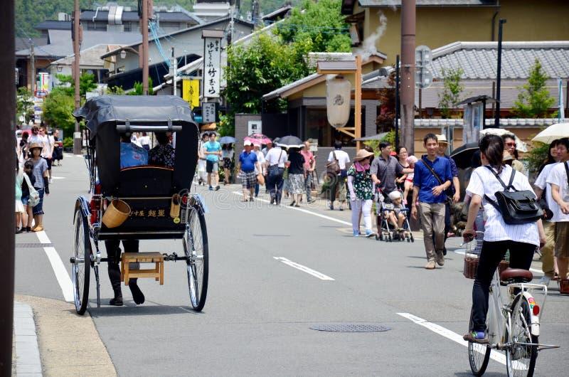 Handelsresandebruksrickshawen för turnerar runt om arashiyamastad arkivfoton