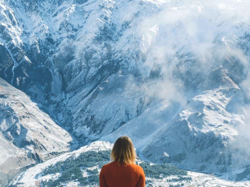 Handelsresandeflicka som ser de snöig bergen som tillbaka står arkivfoton