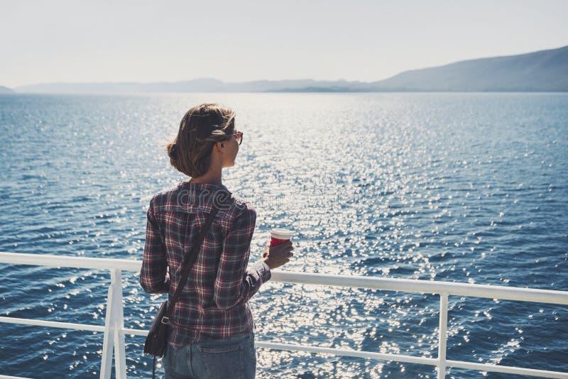 Handelsresandeflickaanseende p? f?rjan som ser havet och rymmer en kaffekopp, ett lopp och ett aktivt livsstilbegrepp arkivfoto