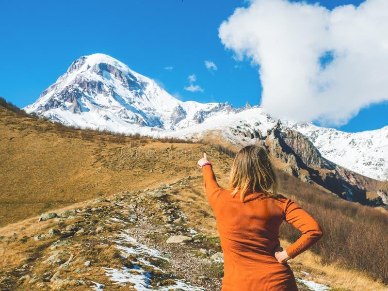 Handelsresandeflickapunkter till överkanten av berget som tillbaka står royaltyfri fotografi