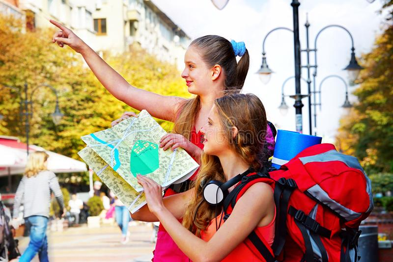 Handelsresandeflickor med ryggsäcken som söker efter den turist- pappers- översikten för väg arkivbild