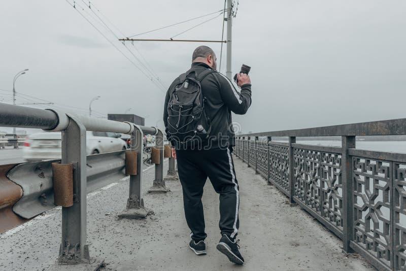 Handelsresandefotografen med kameran och ryggsäcken promenerar bron isolated rear view white arkivbild