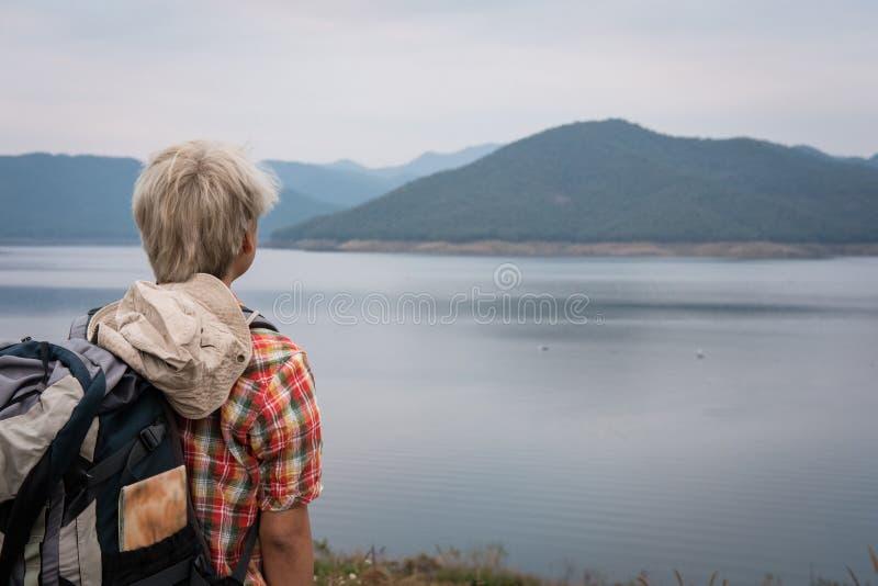 Handelsresandefotvandrareman med ryggsäcken som fotvandrar nära sjön turist- backp royaltyfri fotografi