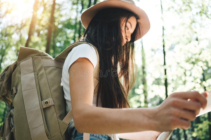 Handelsresandehipsterkvinnan med ryggsäcken och hatten rymmer, i handlägeöversikten och sökande som är riktnings bland träd i sko arkivbilder