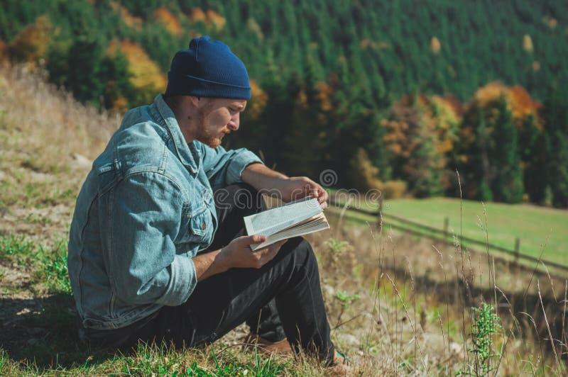 Handelsresandeläsebok för ung man, utomhus- berg på bakgrundssommarsemestrar och livsstilbegrepp royaltyfri fotografi