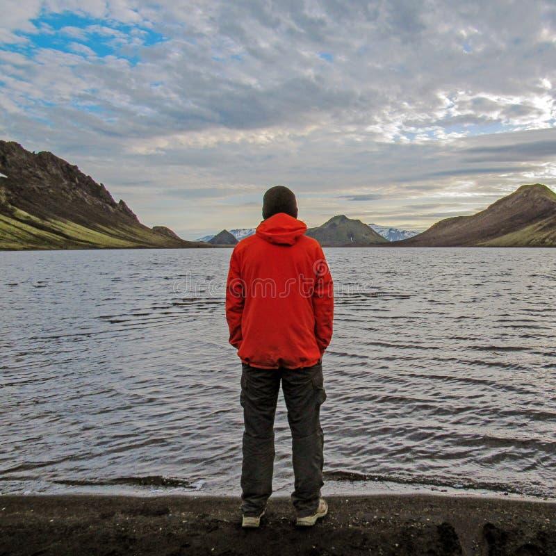 Handelsresandeman i det orange laget som står tillbaka utomhus- se fridfull solnedgångsikt av Altavatn sjön och vulkaniska berg i arkivbild