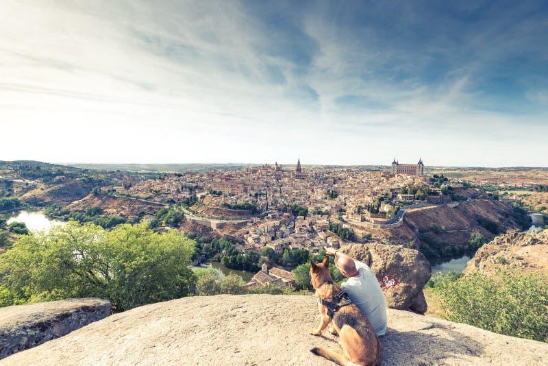 Handelsresandeman och hund som håller ögonen på Toledo cityscape från kullen royaltyfria bilder
