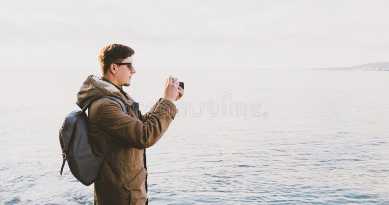 Handelsresandeman som tar fotografier på stranden i vår arkivfoton