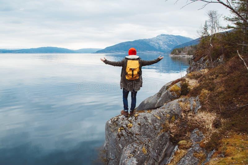 Handelsresandemannen med en gul ryggsäck som bär en röd hatt som står på, vaggar händer på sidan på bakgrunden av berget fotografering för bildbyråer