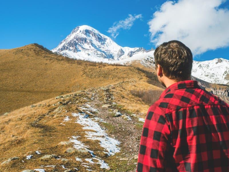 Handelsresandemannen ser upptill av berget och att stå tillbaka arkivfoto
