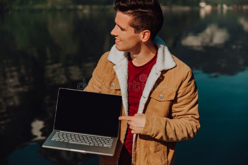 Handelsresandemannen som kopplar av på fartyget som använder bärbara datorn, i att förbluffa naturlandskap, vaggar bergön på sjöb arkivfoto
