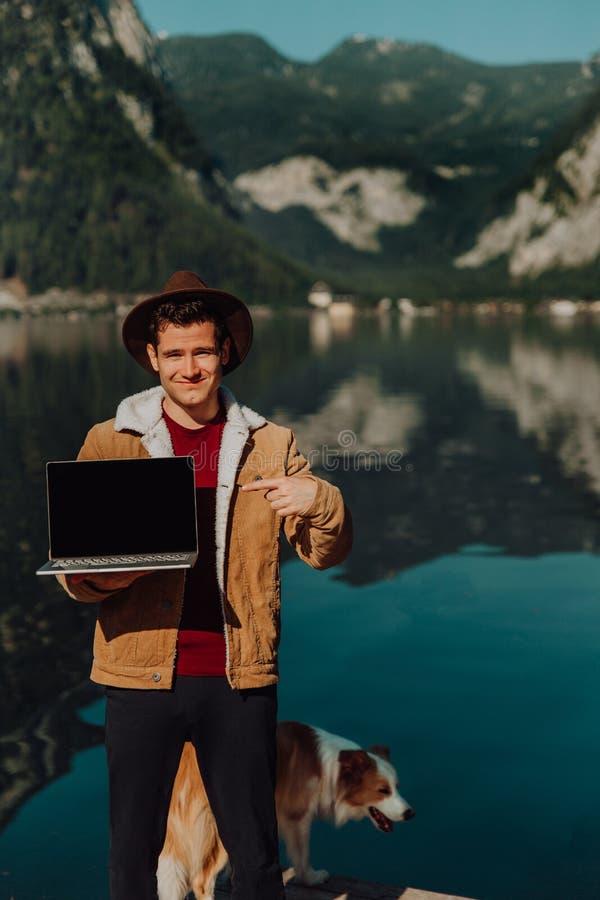 Handelsresandemannen som kopplar av på fartyget som använder bärbara datorn, i att förbluffa naturlandskap, vaggar bergön på sjöb arkivbilder