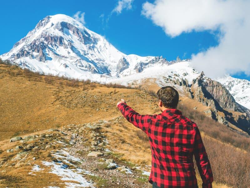 Handelsresandemanpunkter till överkanten av berget som tillbaka står royaltyfri bild