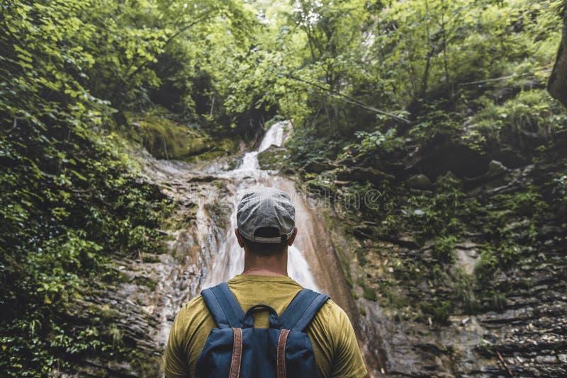 Handelsresanden har nått destinationen och tycka omsikten av vattenfallet och skönhet den ofördärvade naturen Begrundandeaffärsfö royaltyfri bild