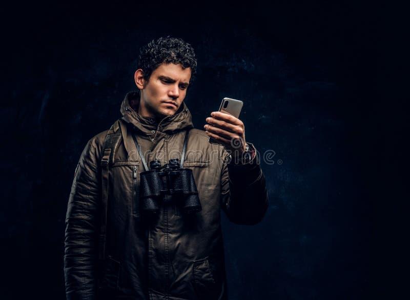 Handelsresanden, i att fotvandra kugghjulet med kikare, använder GPS navigering på hans smartphone i studion mot en mörk vägg arkivfoto