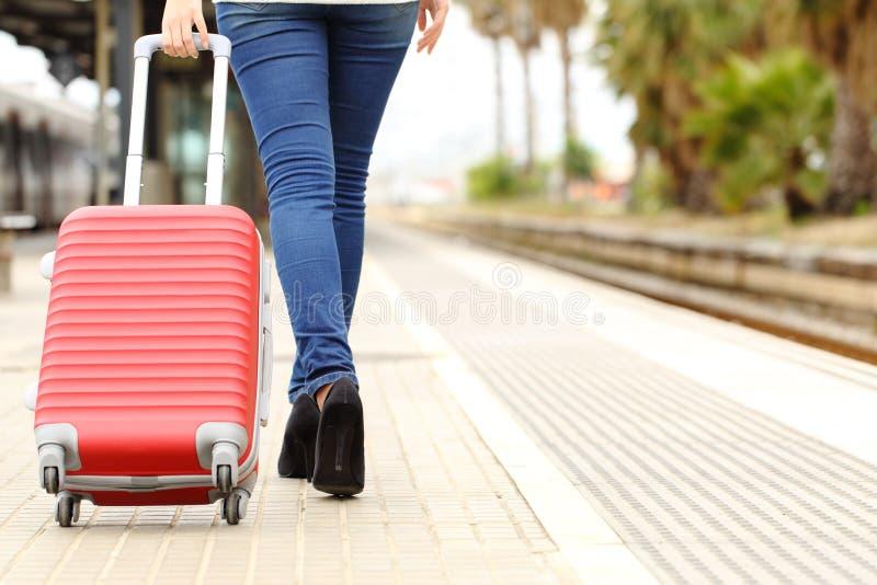Handelsresanden lägger benen på ryggen gå bärande bagage i en drevstation royaltyfria foton