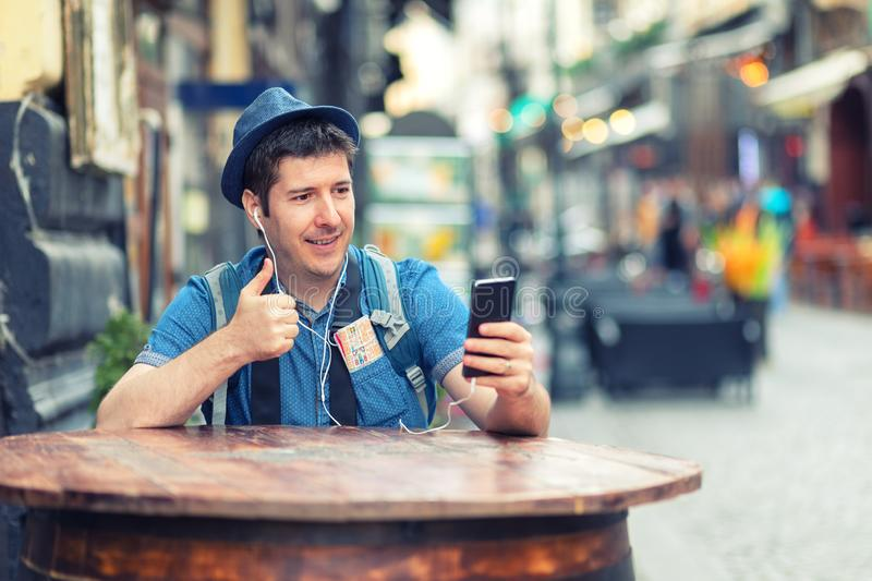 Handelsresanden med den moderiktiga blicken som har en video appellvisningtumme upp stund, tycker om undersökning gator av storst royaltyfria bilder