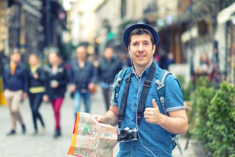 Handelsresanden med den moderiktiga tummen för visningen för blickinnehavöversikten upp på gatan mycket av restauranger och shopp royaltyfria foton