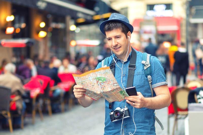 Handelsresanden med moderiktig blick genom att använda översikten på gatan mycket av restauranger och shoppar av europeisk stad royaltyfri foto