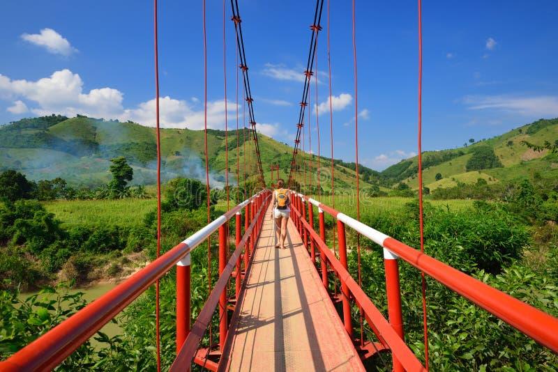 Handelsresanden passerar floden på en upphängningbro. Vietnam arkivbilder