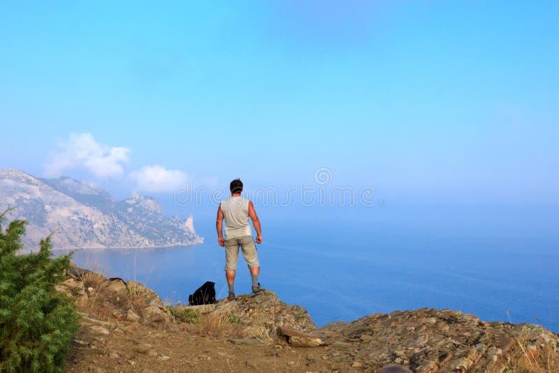 Handelsresanden ser den härliga seascapen från bergöverkanten arkivfoton