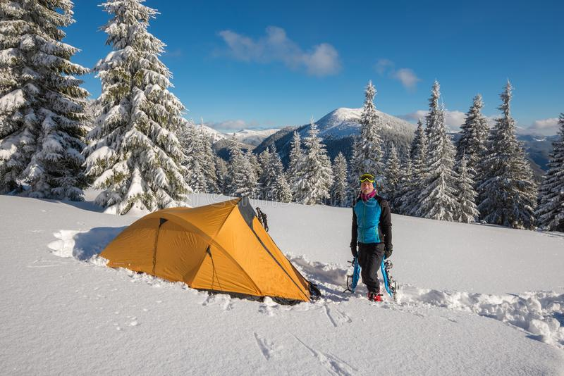 Handelsresanden står i en djup snö nära ett tält royaltyfri bild