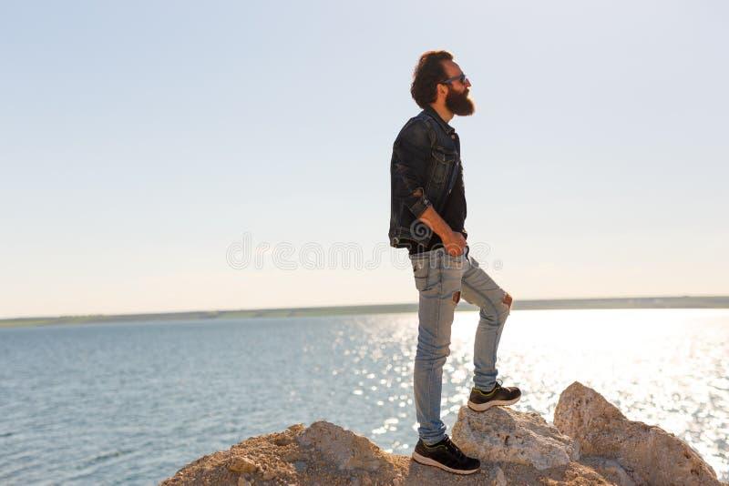 Handelsresanden står på vaggar mot fridsamma vågor för ett härligt hav, en stilfull skäggig hipsterpojke som poserar nära ett lug royaltyfria foton