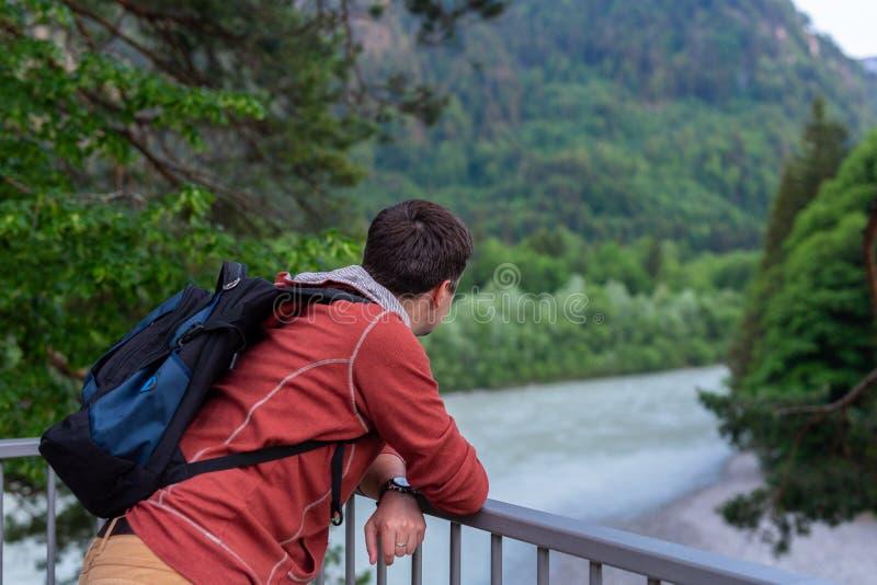 Handelsresandest?llningar f?r ung man n?ra f?ktning v?nde hans baksida till floden och skogen med en ryggs?ck och att se fram?tri royaltyfria foton