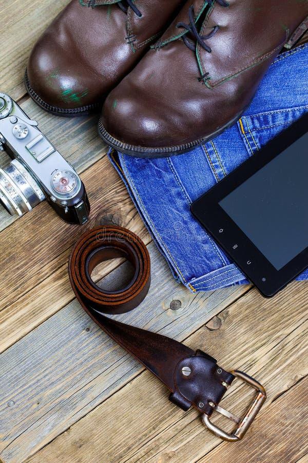 Handelsresandeuppsättning med ett läderbälte, en digitizer, en kamera, en jeans och ett b arkivfoto