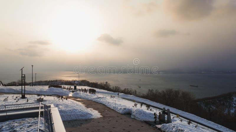 Handelsresandevänner är det en romantisk atmosfär Medan hålla ögonen på solnedgången på den hakodate fjärden under insnöad vinter royaltyfri fotografi
