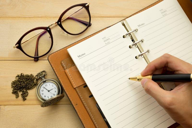 Handen önskar att skriva något och tillbehören för pålagt trä för arbete arkivfoton